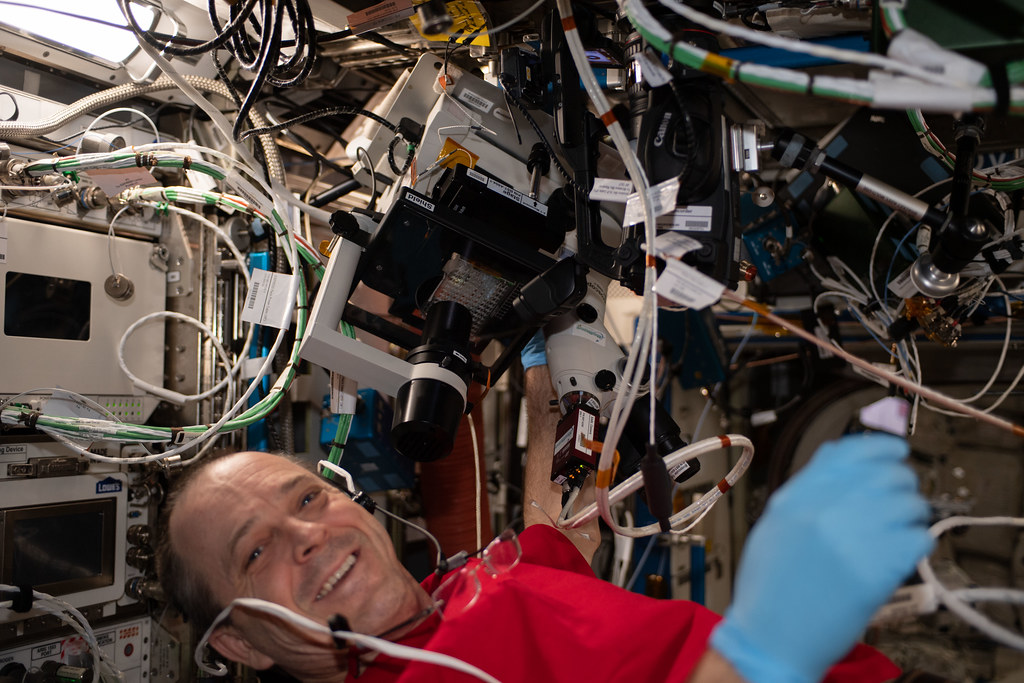 NASA Astronaut Ricky Arnold performs microscope photo document operations