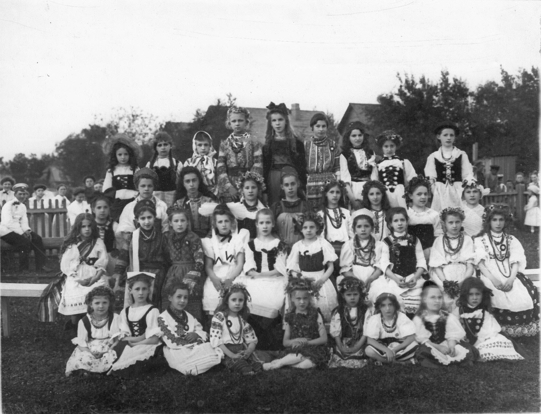 Группа детей в национальных костюмах на спортивной площадке гимнастического общества «Пальма»
