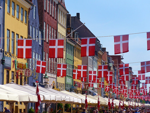 Danish flags and the colourful houses of Nyhavn in Copenhagen, Denmark