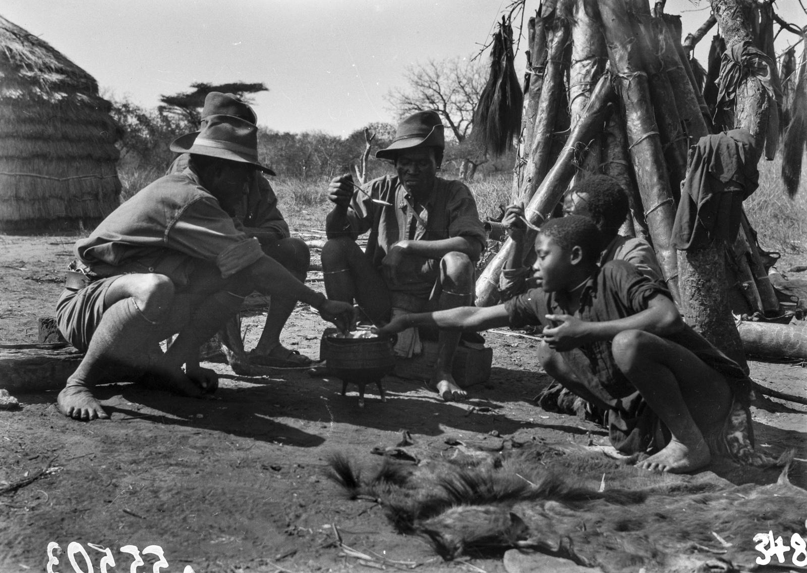Южно-Африканский Союз. В окрестностях Претории.  Участники экспедиции и дети в поселении во время еды