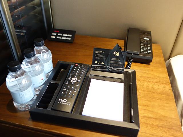 床頭櫃有電話、電源面板、遙控器、紙筆、礦泉水@高雄H2O水京棧國際酒店