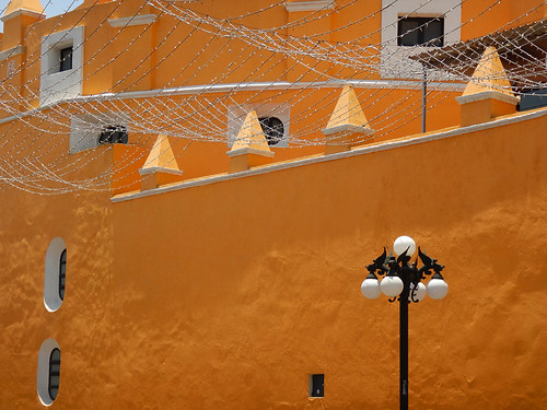 A streetlamp with dragons against a yellow wall in Puebla, a UNESCO Heritage site in Mexico