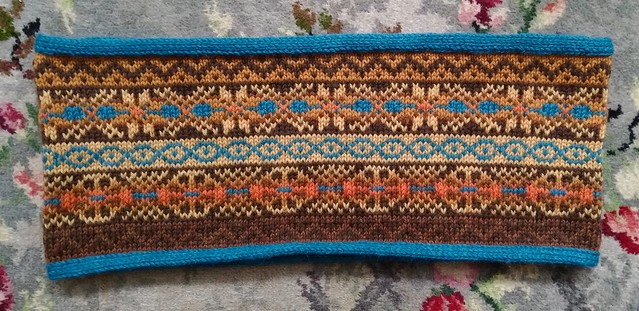 Flatlay of a handknit fair isle cowl, in orange, yellow, blue and brown.
