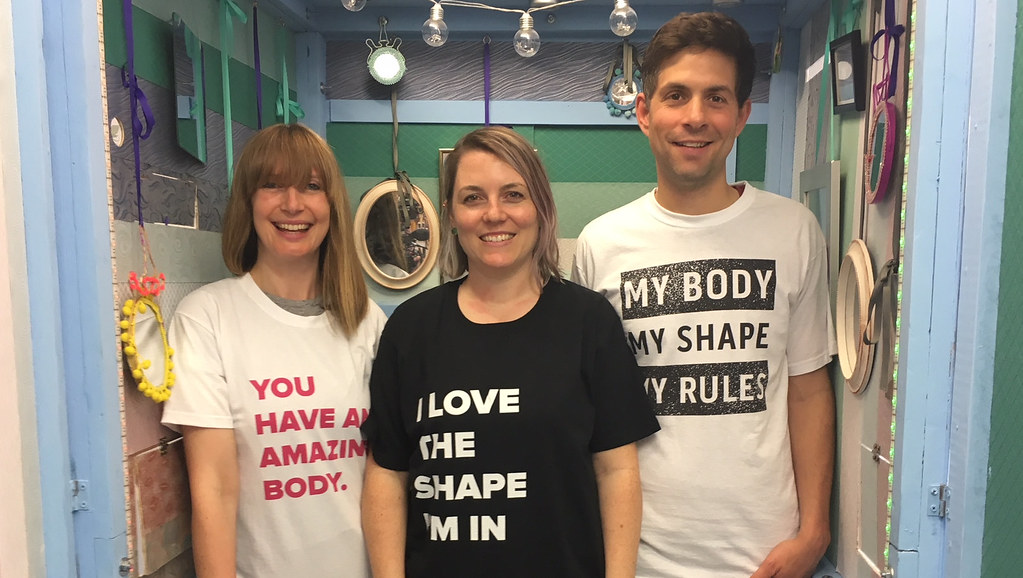 A man and two women standing in a cubicle with positive body image slogans on their T-shirts