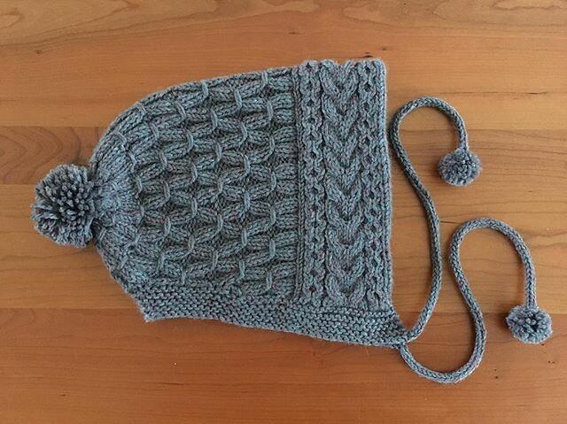 Putting the finishing touches on my ski bonnet. #knitting #neonskibonnet #pompoms #hatknitting