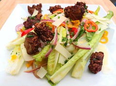 SALAD OF CRACKED PEPPER -DUSTED CHICKEN LIVER NUGGETS, SHREDDED PARMIGIANO REGGIANO, ROMAINE, MILD CHILLIES AND RED ONIONS