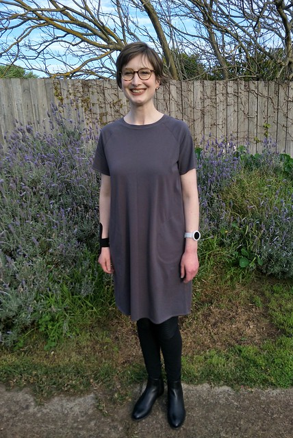 Woman stands in front of garden fence. She wears a short-sleeve, grey knit boxy tee dress with pockets, black leggings and black ankle boots. She is smiling.