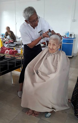 An elderly resident receives a hair cut from the Home's Manager. (Courtesy of Twilight Villa) )