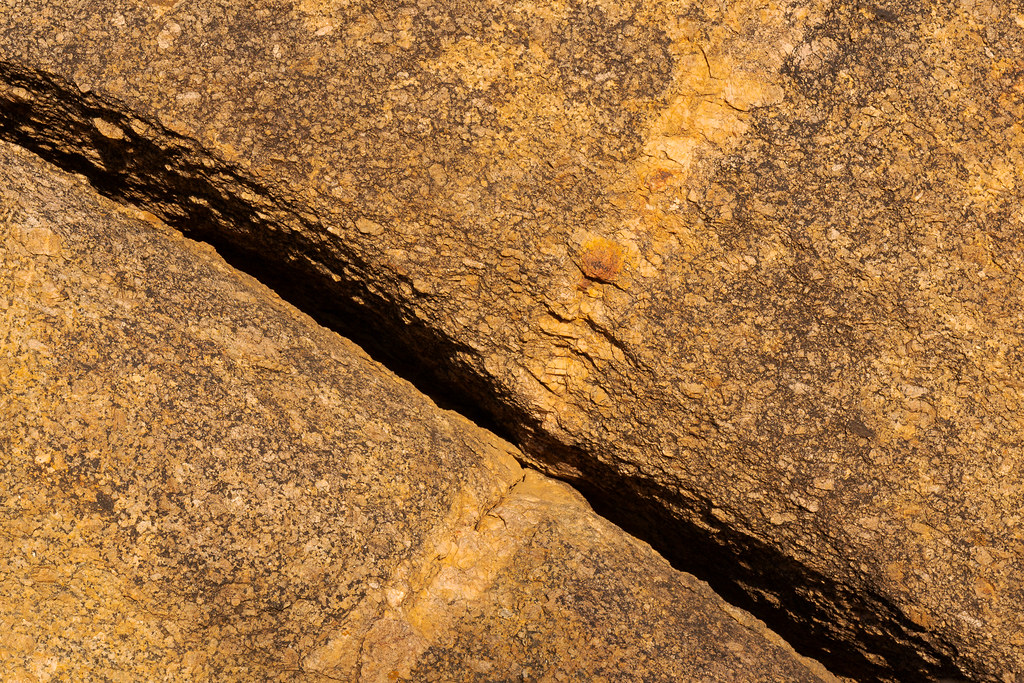 A large crack runs through a granite boulder in one direction while a thick line of a different type of rock runs in the other direction