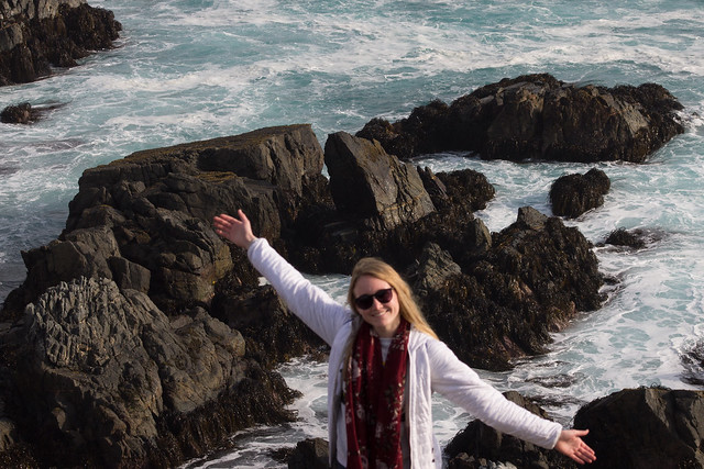 Student stands in from of large grey coastal rocks by the coast of Quintay, Chile, with arms spread wide open.