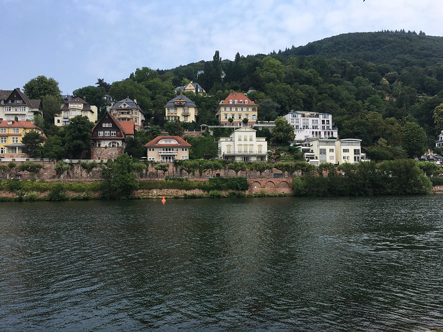 View of yellow and white houses and buildings on the edge of river .