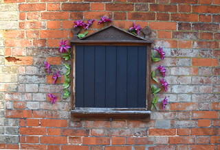 'Eye Borough Cemetery': notice board with plastic passionflowers
