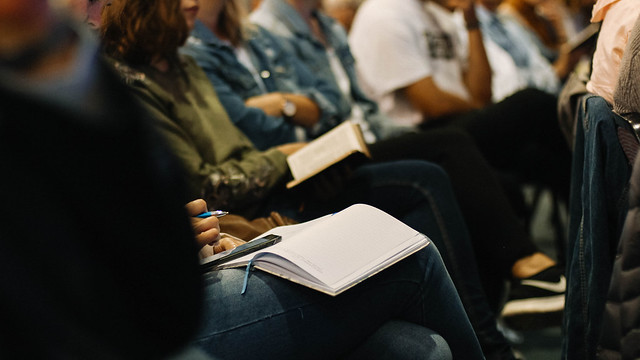 Group of people sitting down taking notes in a conference.