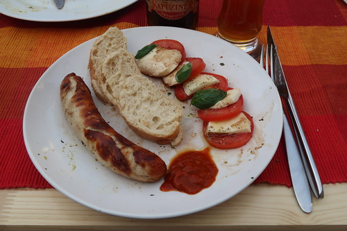 Bratwurst mit Ketchup, Baguette und Mozzarella-Tomaten