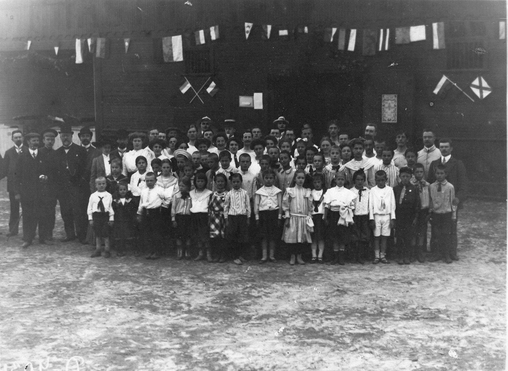 Группа детей и взрослых членов гимнастического общества «Пальма» на спортивной площадке