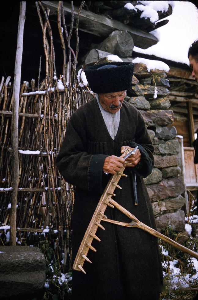 Мужчина в архалуке занимается починкой граблей