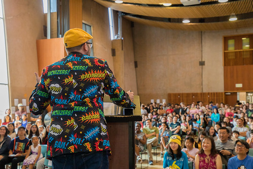Matt Silady at a podium speaking to a crowd, his blazer is covered in comic book actions like BAM! and WOWZERS!