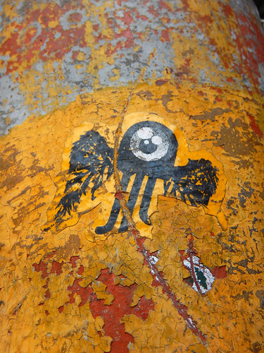 Graffiti with a little winged eye on a decaying yellow wall in Puebla, a UNESCO Heritage site in Mexico