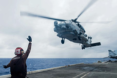 PHILIPPINE SEA (Sept. 20, 2018) A Sailor assigned to Helicopter Maritime Strike Squadron (HSM) 77 directs an MH-60R Sea Hawk as it launches from the flight deck of the Navy's forward-deployed aircraft carrier USS Ronald Reagan (CVN 76) during Valiant Shield 2018. The biennial, U.S. only, field-training exercise focuses on integration of joint training among the U.S. Navy, Air Force and Marine Corps. This is the seventh exercise in the Valiant Shield series that began in 2006. (U.S. Navy photo by Mass Communication Specialist 2nd Class Kenneth Abbate)