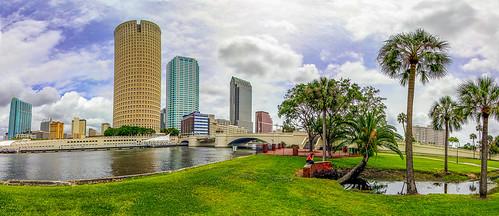 sky cloud river city buildings grass trees