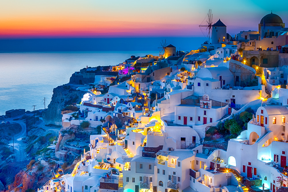 Travel Concepts. Skyline of Oia Town with Traditional White Architecture and Iconic Windmills in Village of Santorini in Greece.