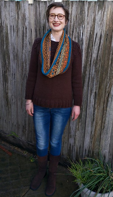 A woman stands in front of a fence. She wears a handknitted, fair isle cowl, handknitted brown jumper, jeans and brown suede boots.