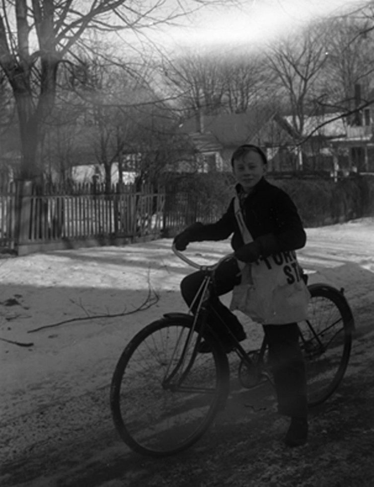 A boy on a bicycle with a Toronto Star newspaper carrier bag. Whitby, Ontario. Photo taken by Marjorie Georgina Ruddy on February 6, 1940.
