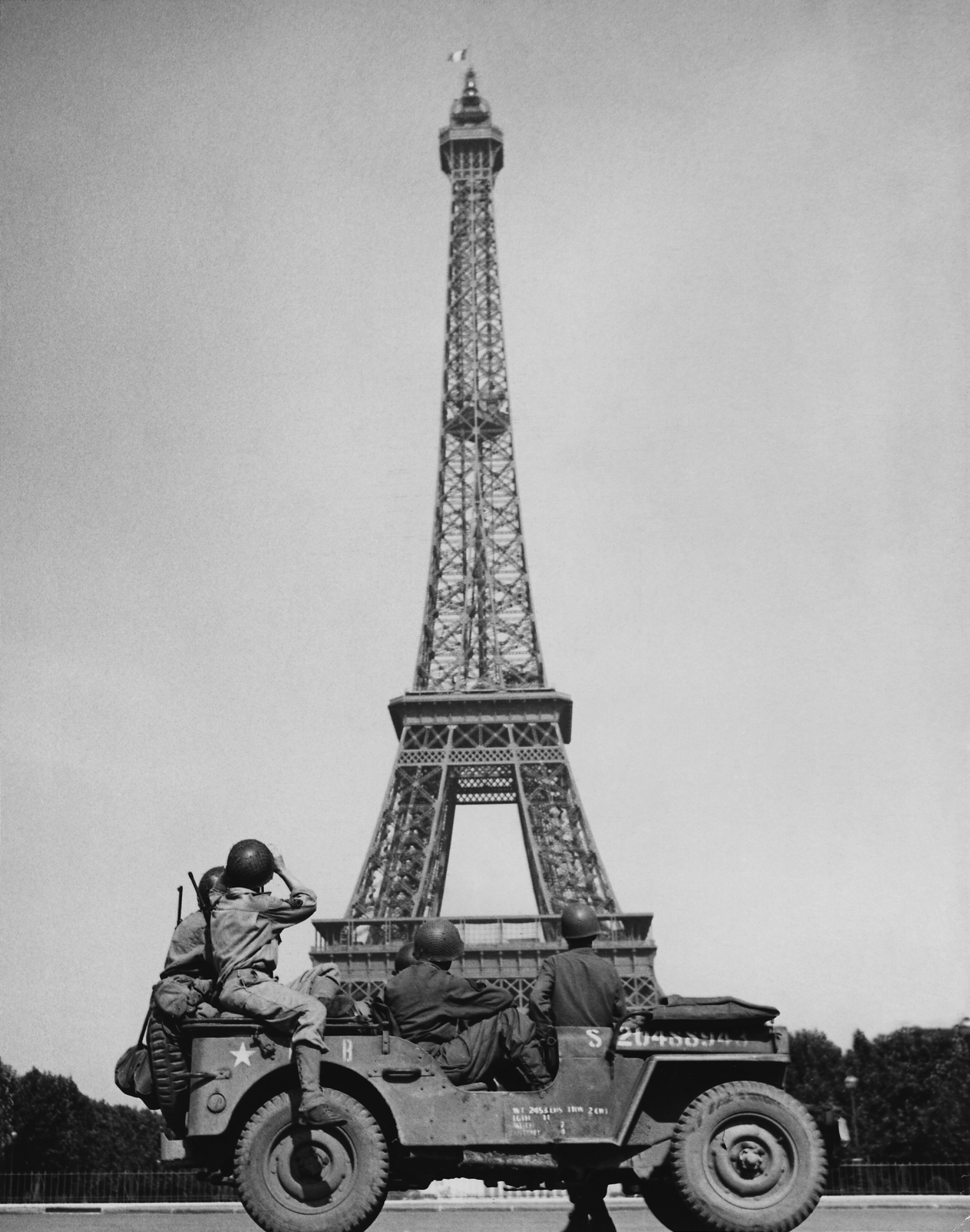 American soldiers watch as the French Tricolor flies from the Eiffel Tower again. Photo taken circa August 25, 1944. from the National Archives and Records Administration.