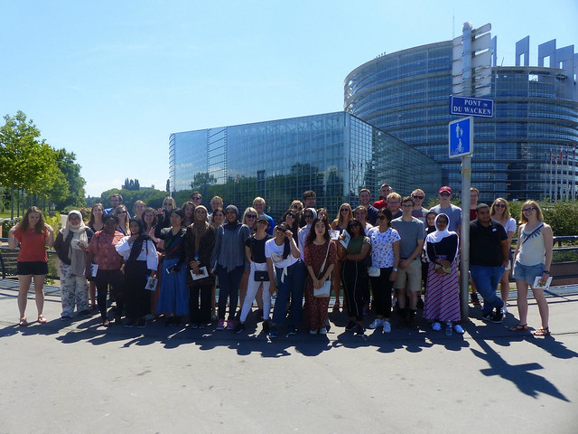 Several dozens of students standing in front of large glass parliament building.
