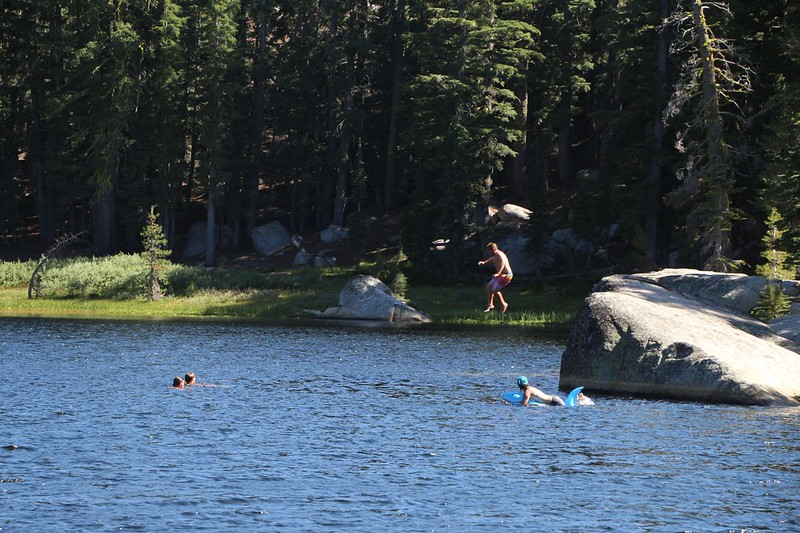 Students from Sierra Nevada College swimming and jumping into Rubicon Lake from a large boulder