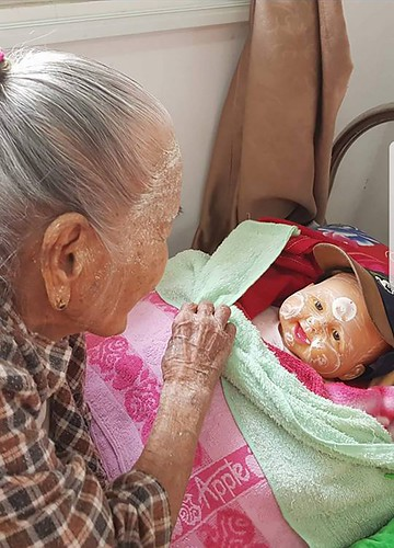 88 years old Tin Tin spends much of time attending to her companion baby doll, her best friend.(Courtesy of Twilight Villa)