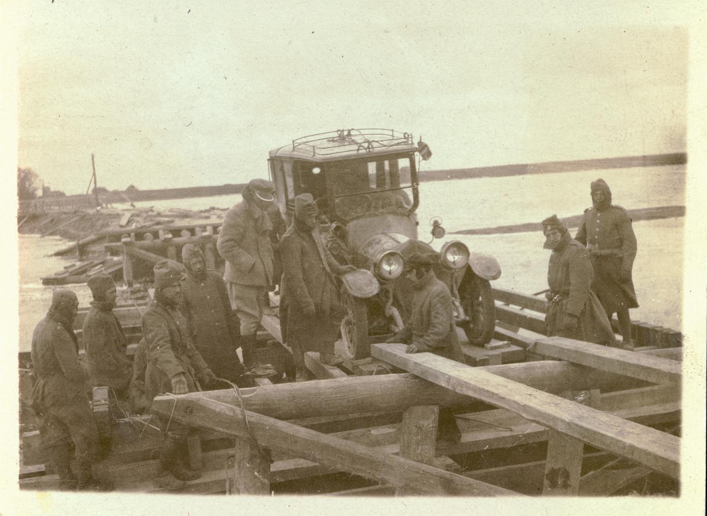 Мужчины, занятые погрузкой на мост автомобиля Объединенного распределительного комитета в ходе полевого выезда в Польше
