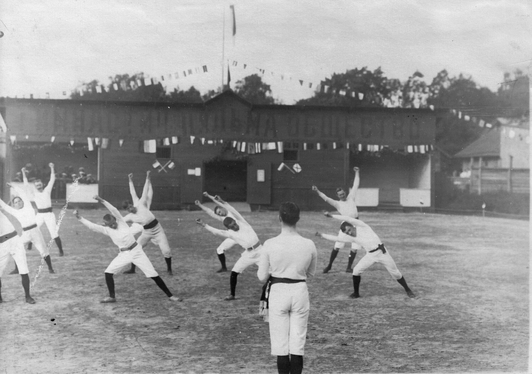 Группа членов Гимнастического общества «Пальма» делает вольные упражнения на спортивной площадке