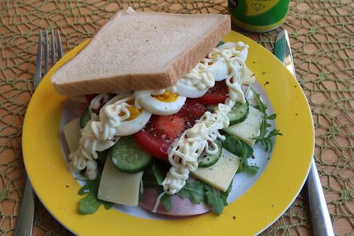 Sandwich mit Kochschinken, Ruccola, mittelaltem Gouda, Gurkenscheiben, Tomatenscheiben, gekochtem Ei und Sandwichcreme