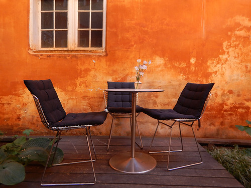 An orange wall with table and comfy chairs in Copenhagen, Denmark