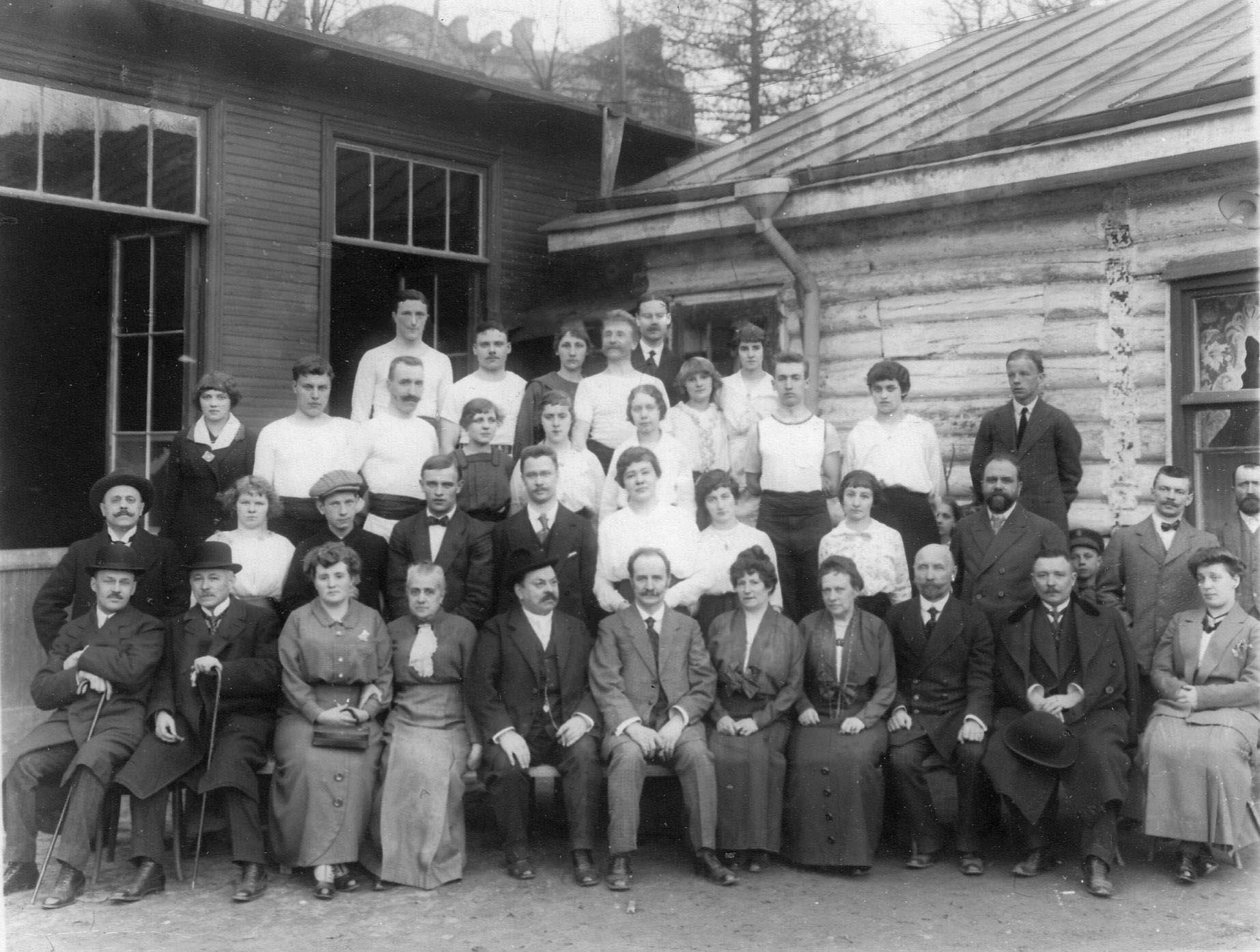 Группа членов гимнастического общества «Пальма» и их родственники у дачного строения