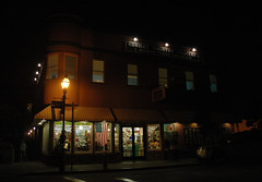 American flag hangs in the window, night, Cunha's Country Grocery & Second Floor Emporium, Half Moon Bay, California, USA