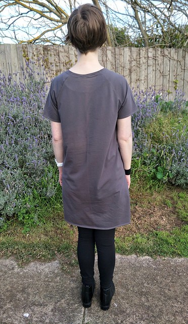 Woman stands in front of garden fence. She wears a short-sleeve, grey knit boxy tee dress with pockets, black leggings and black ankle boots. Her back is to the camera.