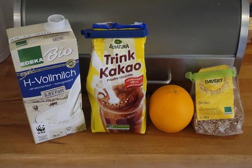 Zutaten für einen Frühstücksbrei aus frisch geflocktem Dinkel, Kakao und Orangenstückchen