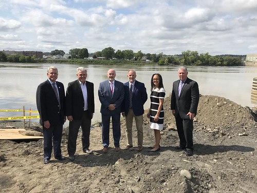 State and local officials stand side by side. The Hudson River and the waterway's western bank is visible behind. Left to right: NYS Canal Corporation Director Brian Stratton, Rensselaer County Executive Steve McLaughlin, Troy Mayor Patrick Madden, NYS DEC Deputy Commissioner Martin Brand, Deputy Secretary of State Kisha Santiago, NYS Assemblymember John McDonald