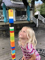 Madeleine smiles at her tall duplo tower at dinner