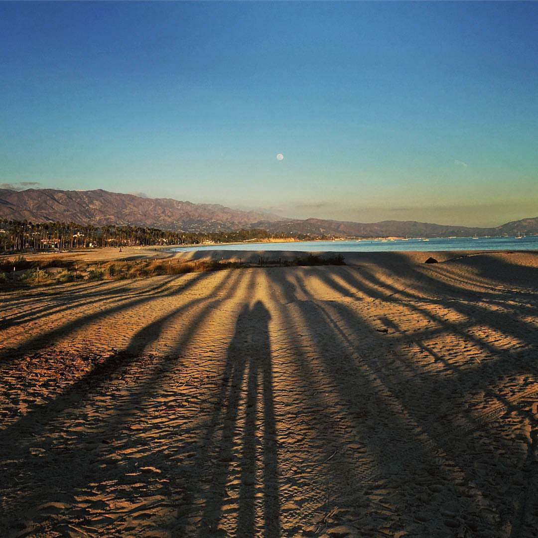 https://www.instagram.com/p/BfxGzU5F_MT/ Long shadows of a couple along a sandy beach with the moon in the evening sky