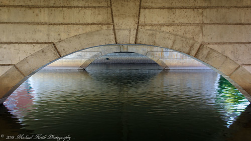 bridge concrete water river calm arches repetitive batavia canon 1200d rebelt5 efs24 wide wideangle flow lines pattern line repeat ripples reflections tan green foxriver red yellow blue under underneath shapes arch reflection ripple texture angles