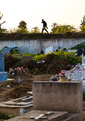 Angolan man walking o the wall of an old cemetery, Benguela Province, Catumbela, Angola