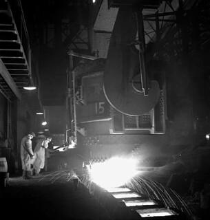 Workman taps out an open-hearth furnace to pour molten steel into ingot moulds... / Un ouvrier prélève de l'acier en fusion d'un four à creuset ouvert pour le couler dans des moules à lingots...