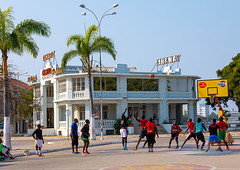 Angolan men playing basket ball in front of the old portuguese colonial tamariz casino, Benguela Province, Lobito, Angola