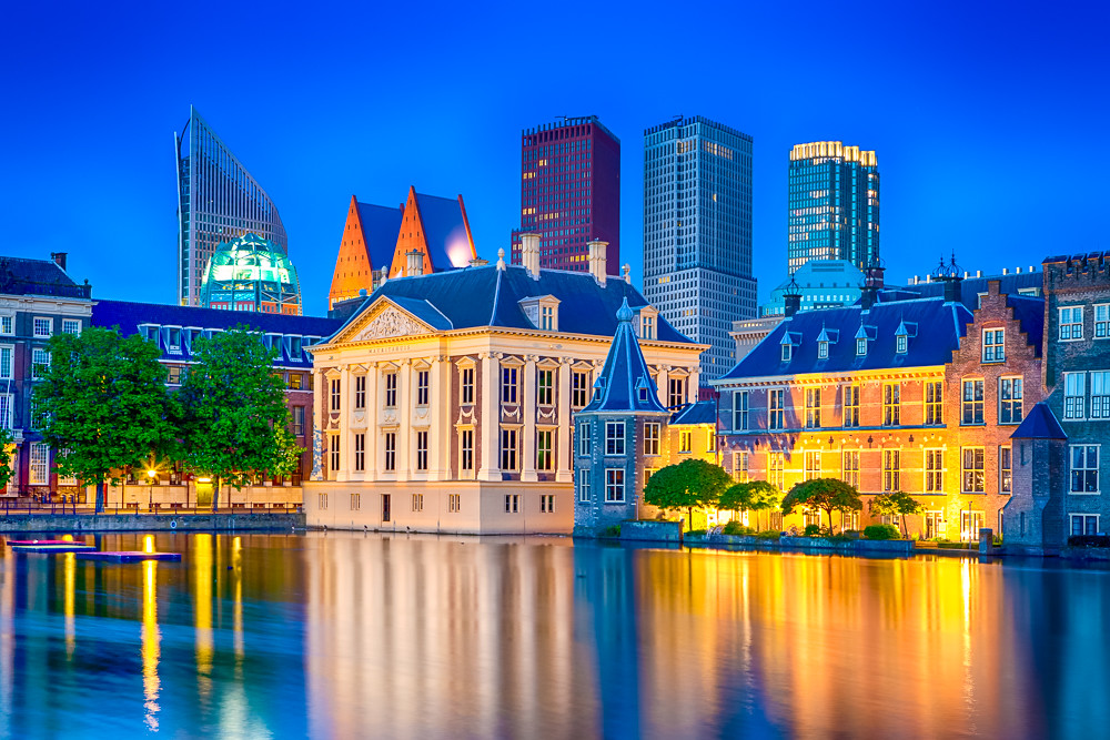 Travel Ideas. Binnenhof Palace of Parliament in The Hague in The Netherlands at Blue Hour. Against Modern Skyscrapers.