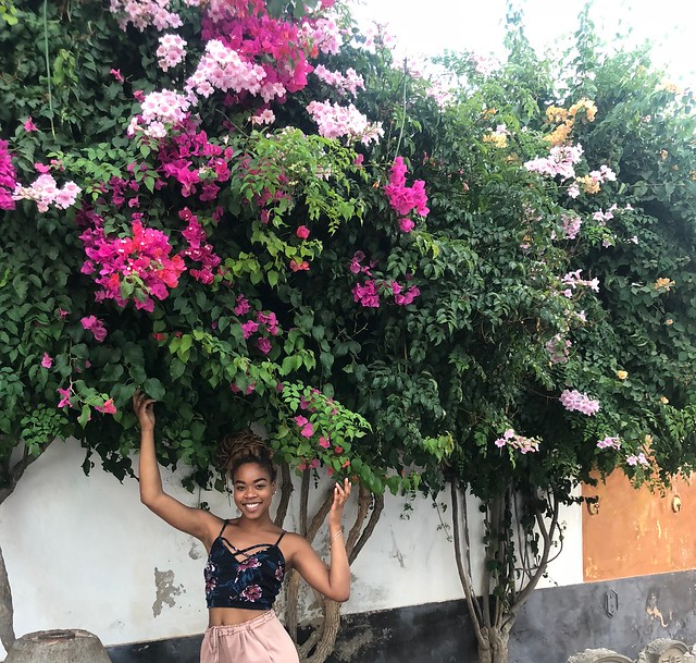 Student posing in front of big tree with bright and pale pink flowers.