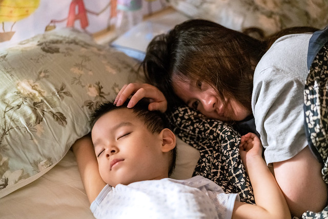 Portrait of mother watching her son sleeping at home, Shanghai, China, Sep 2, 2018