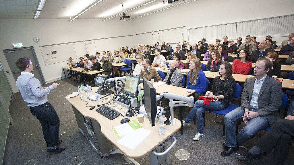 A maths seminar in progress in a crowded lecture room